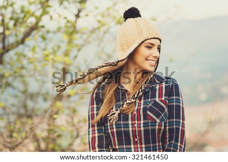 Beautiful modern urban young woman wearing blue and red plaid shirt and knitted beige and black hat. Trendy teenage girl in autumn outdoors. Horizontal, medium retouch, matte filter. - stock photo