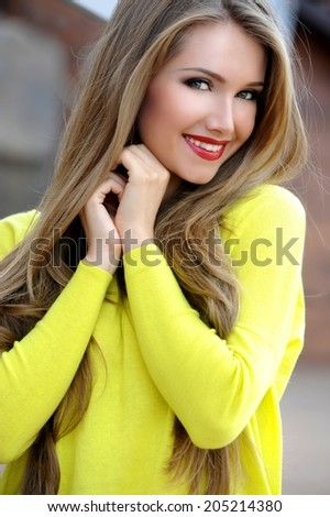 Beautiful modern woman with long hair in a sweater outdoors - stock photo