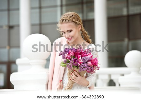 Beautiful modern young woman in springtime. Girl with bouquet of tulips and lilac. - stock photo
