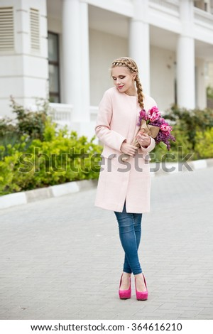 Beautiful modern young woman in springtime. Woman with bouquet of tulips and lilac.