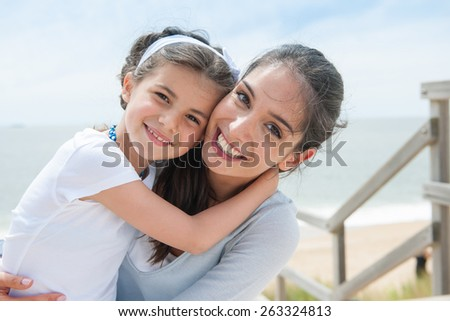 beautiful mom and her daughter at seaside smiling at camera