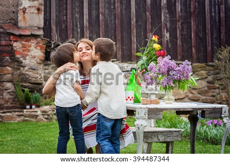 Beautiful mom, having coffee in a backyard, young cute child giving her present and flowers for her birthday. Mother day concept, love, happiness, cozy atmosphere