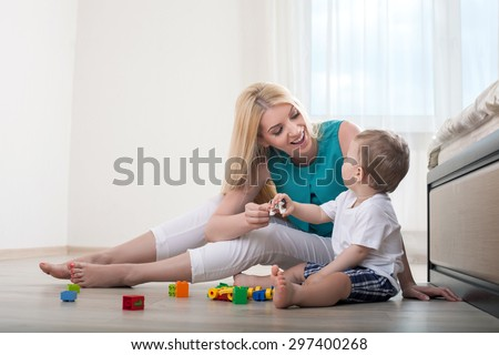 Beautiful mom is spending time with her baby in bedroom. They play with toys. The parent and her chills are looking at each other and smiling - stock photo