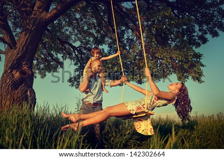 Beautiful mom on the swing in the forest with her family  - stock photo