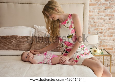 Beautiful Mom playing with her daughter in bedroom.  Parent and little kid relaxing at home. Family having fun together. - stock photo