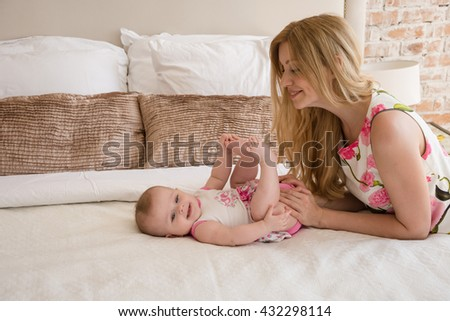 Beautiful Mom playing with her daughter in bedroom. Parent and little kid relaxing at home. Family having fun together. Love, trust and tenderness concept.