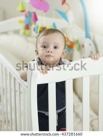 Beautiful 9 months old baby boy standing in white crib at bedroom - stock photo