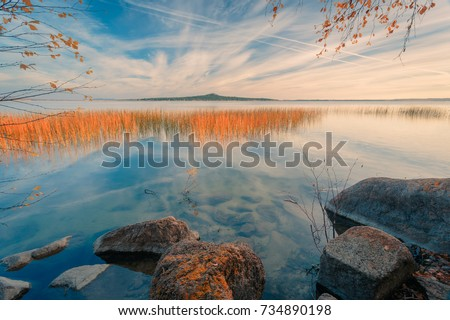Beautiful morning autumn landscape. Stones and reeds on the lake shore in the morning sunlight. North Kazakhstan.