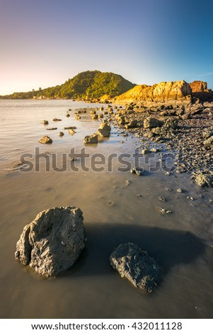 beautiful morning light on rocks in water at coastline  - stock photo
