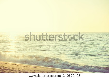 Beautiful morning sunrise over a calm ocean coastline. Horizontal view of small waves crashing on the beach - stock photo
