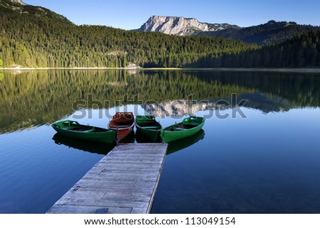 beautiful morning view for mountains, lake and boats in Durmitor national park - stock photo