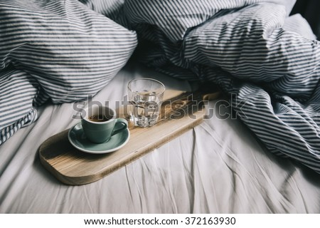 Beautiful morning working in bed essentials: Laptop and a fresh morning coffee on a wooden rustic hand-made tray - stock photo