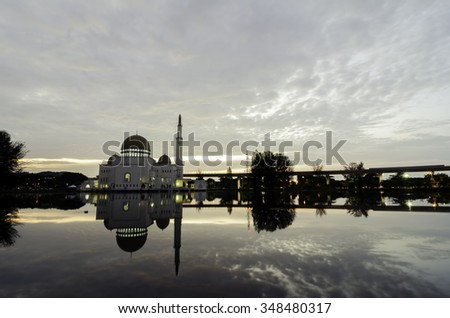 beautiful mosque at sunset sunrise with reflection on the lake and cloudy sky