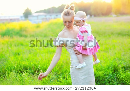 Beautiful mother and baby little daughter wearing a dress in sunny summer day together on sunlight sunset  - stock photo