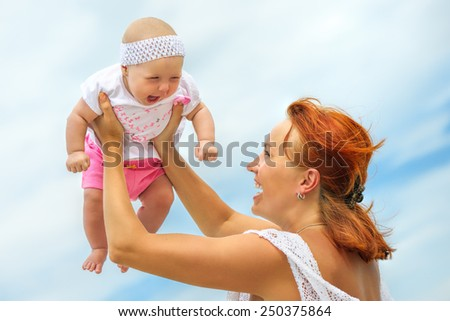 Beautiful Mother And Baby outdoors. Beauty Mum and her Child playing in outdoor together. Outdoor Portrait of happy family. - stock photo