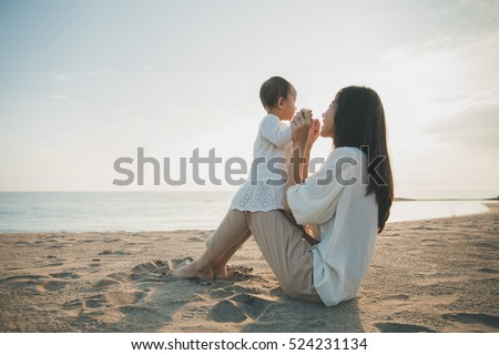 Beautiful Mother And Baby outdoors. Mum and her Child together enjoying sunset