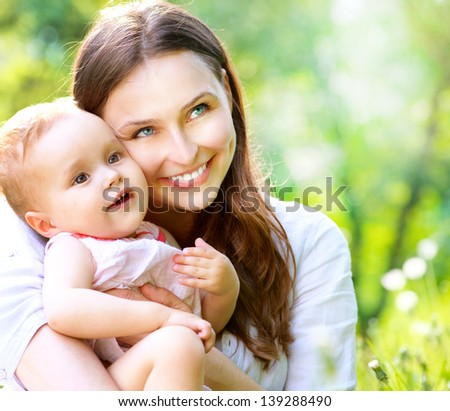 Beautiful Mother And Baby outdoors. Nature. Beauty Mum and her Child playing in Park together. Outdoor Portrait of happy family. Joy. Mom and Baby - stock photo