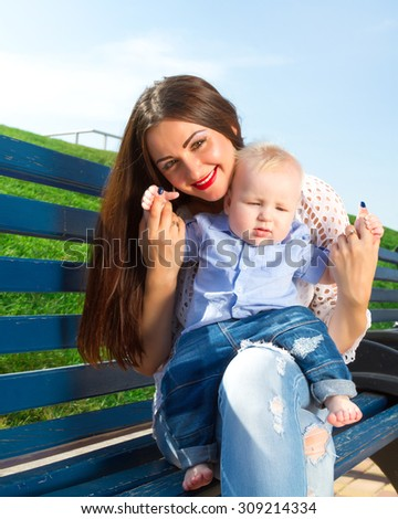 Beautiful Mother And Baby outdoors. Nature. Beauty Mum and her Child playing in Park together. Outdoor Portrait of happy family. Joy. Mom and Baby.Portrait of happy loving mother and her baby outdoors - stock photo