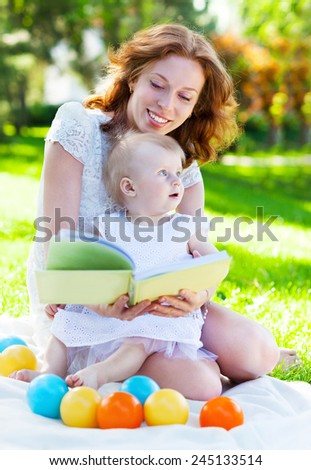 Beautiful Mother And Baby reading outdoors. Happy mum and her Child playing in Park together. Outdoor Portrait of happy family - stock photo