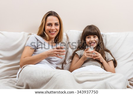 Beautiful mother and daughter are sitting on bed in pajamas and drinking milk.Glass of milk for mother and daughter  - stock photo