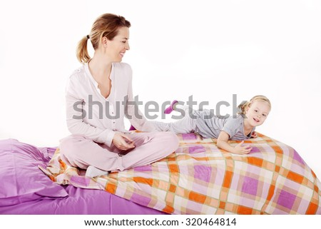 Beautiful mother and daughter enjoying their time in the bed - stock photo
