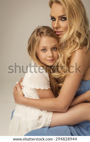 Beautiful mother and daughter hugging each other - stock photo