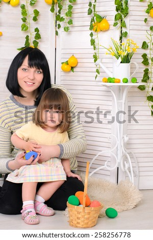 Beautiful mother and daughter in Easter decorations and with basket painted eggs - stock photo
