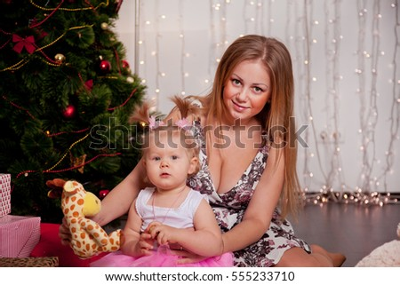 beautiful mother and daughter in front of a Christmas tree