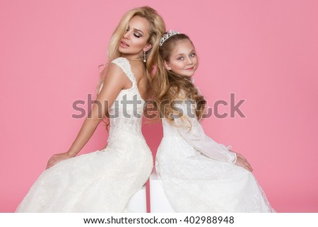 beautiful mother and daughter, little princess, little miss and queen of the blonde with long curly hair sit next to each other in a wedding dress and communion dresses, they look amazing - stock photo