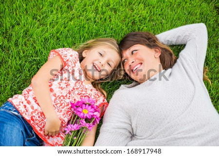 Beautiful mother and daughter lying together outside on grass, Special intimate moment - stock photo