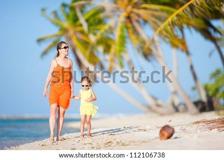 Beautiful mother and daughter on a deserted island - stock photo