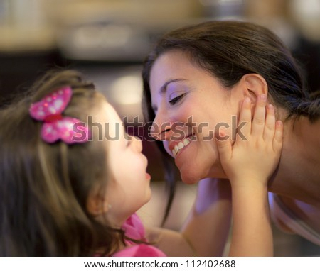 Beautiful mother and daughter share a tender moment - stock photo