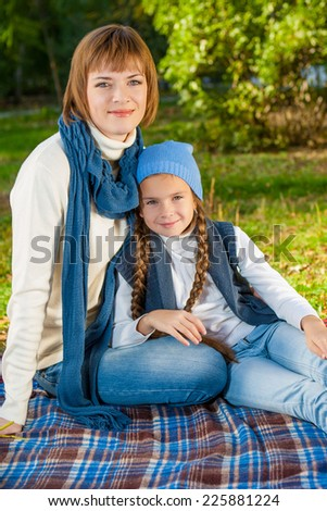 Beautiful mother and daughter sitting on a picnic. In blue white warm clothes.