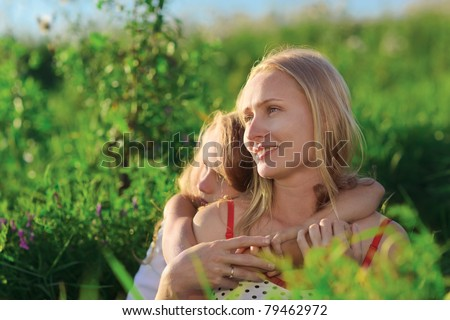 Beautiful mother and daughter sitting on green lush grass meadow in sunset sun beams