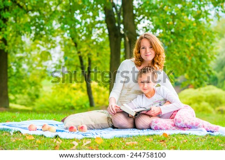 Beautiful mother and daughter spend a weekend at a picnic in the park - stock photo