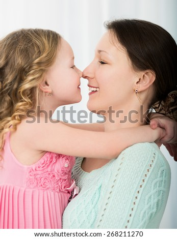 Beautiful mother and daughter touching each other with their noses. Lovely family portrait  - stock photo