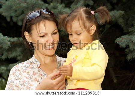 Beautiful mother and daughter went to walk in the forest