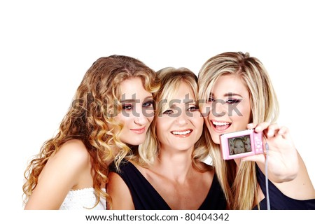beautiful mother and daughters with make-up and long blond hair happy together on a white studio background taking picture with digital camera - stock photo