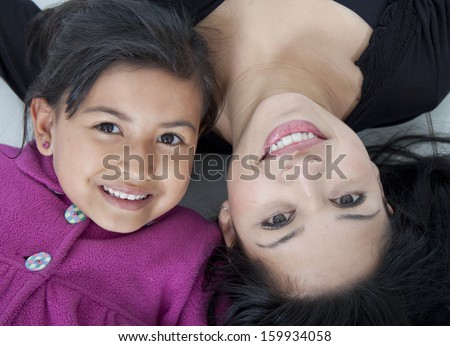 Beautiful mother and daugther on the floor white - stock photo