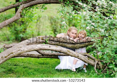 beautiful mother and her daughter in a blooming garden - stock photo
