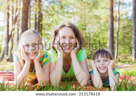 Beautiful mother and her daughters on a bright sunny day.