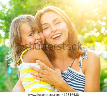 Beautiful Mother And her little daughter outdoors. Nature. Beauty Mum and her Child playing in Park together. Outdoor Portrait of happy family. Joy. Mom and Baby - stock photo