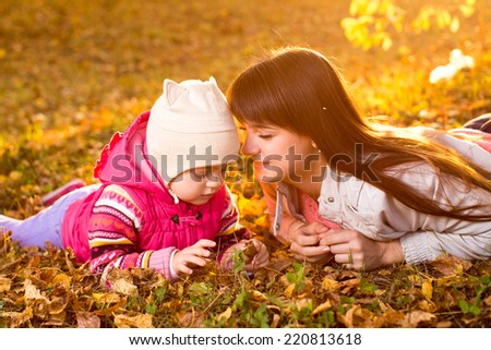 beautiful mother and kid girl laying on autumnal leaves outdoors - stock photo