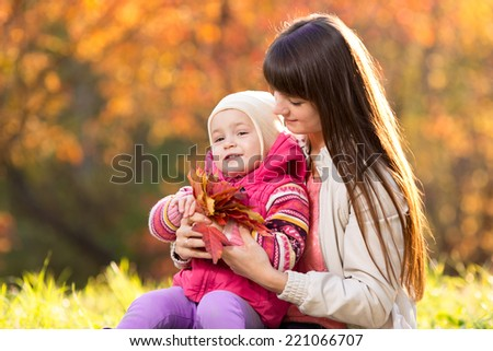 beautiful mother and kid girl with autumnal leaves outdoors