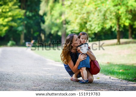Beautiful mother and little daughter walking together in summer park