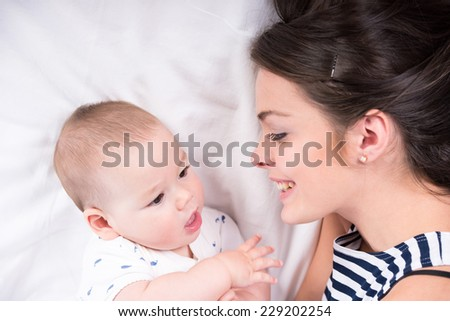 Beautiful mother and son are lying in bed and looking at each other. - stock photo