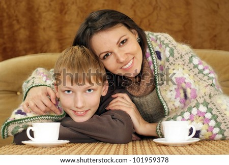 Beautiful mother and son sitting on the couch with a cup on a brown background