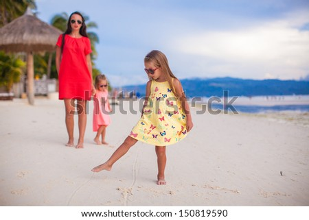 Beautiful mother and two her kids at exotic beach on sunset