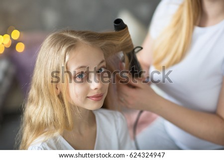 beautiful mother cares about a teenage daughter. Mom curls straightens hair to her daughter, Mom and daughter with long blond hair, concept of tenderness and care in real room