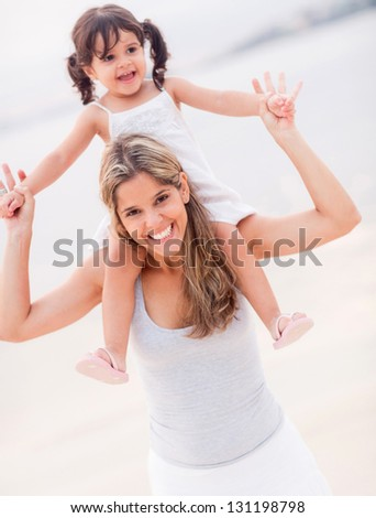 Beautiful mother carrying her daughter on shoulders at the beach